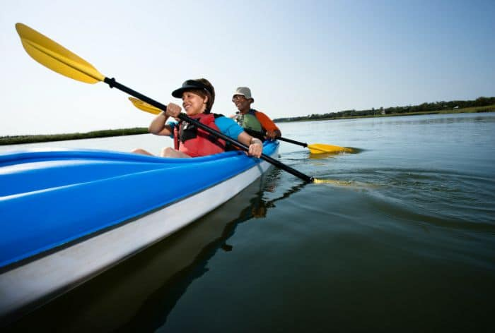 Low angle of African American middle-aged man and woman paddling kayak.