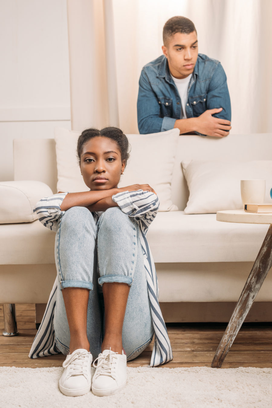 young couple, her sitting on the floor and him standing behind a couch; looking away. Healthy Sexual Relationship