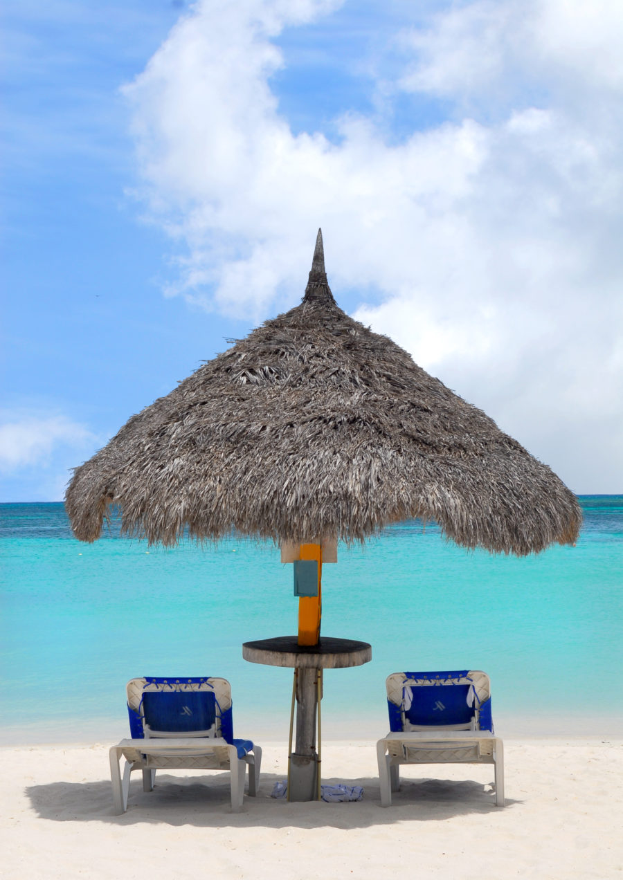 Two chairs on the beach under a grass umbrella - do's and don't for traveling abroad