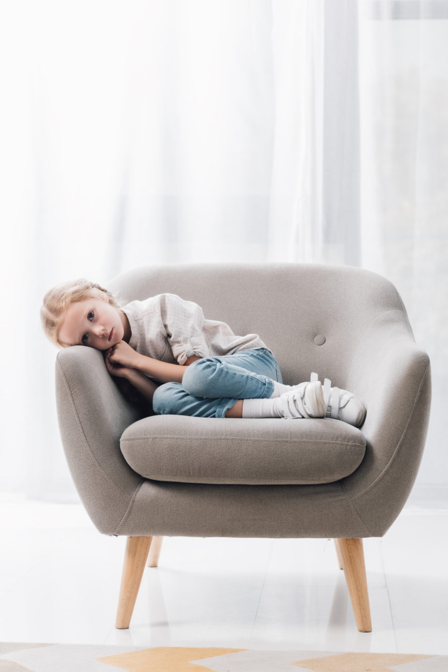 young girls laying in a small chair, sad. Father's Rights and paternity