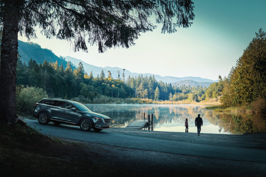 couple walking towards the lake, the 2020 Mazda CX-9 nearby.