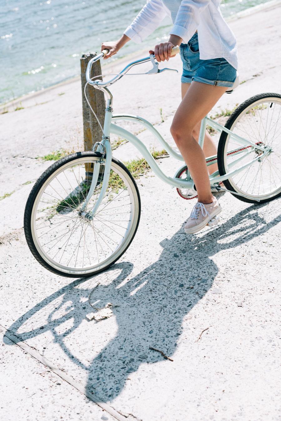 Female riding a bike along the beach