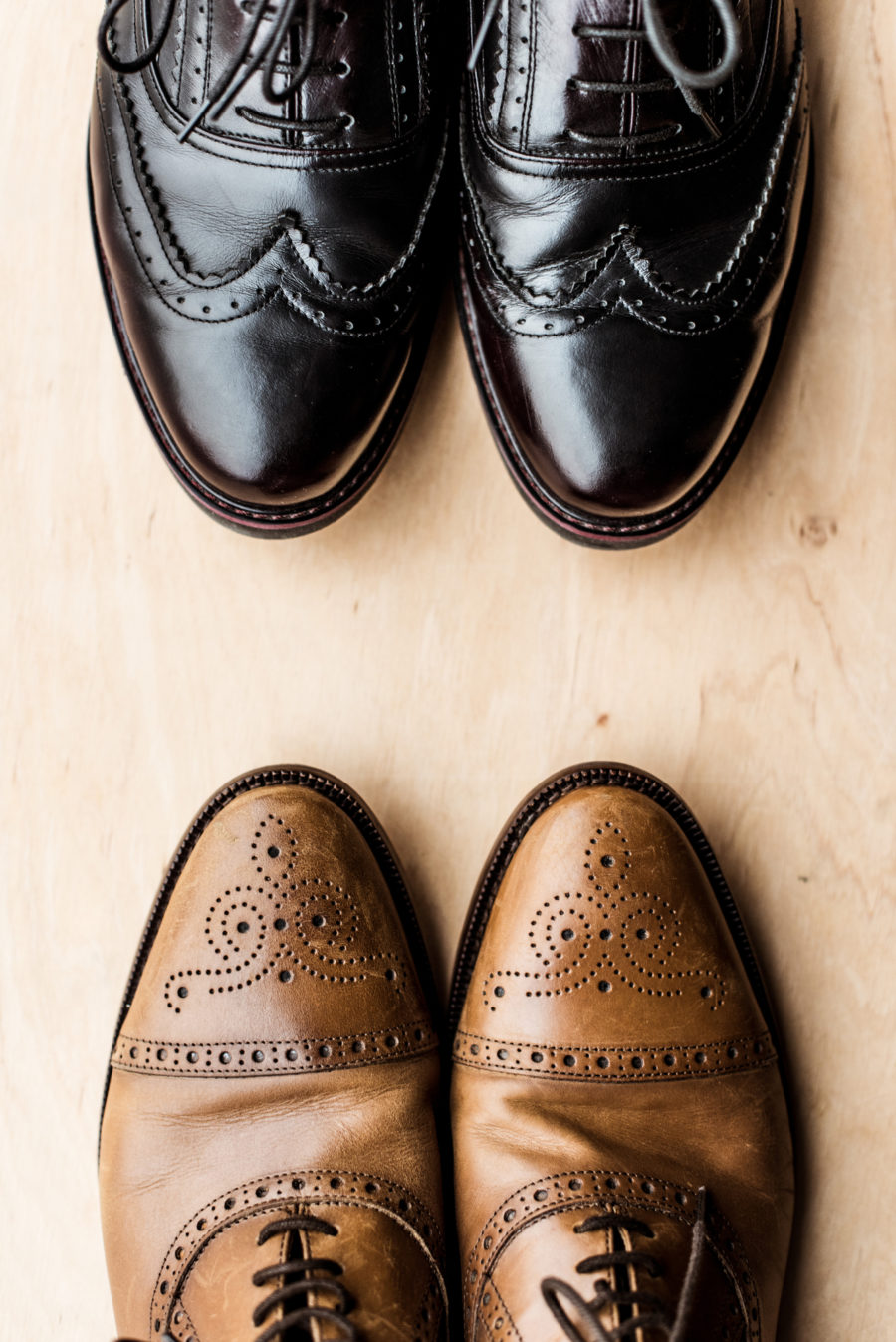 Top view of black and brown pairs of leather shoes on wooden floor