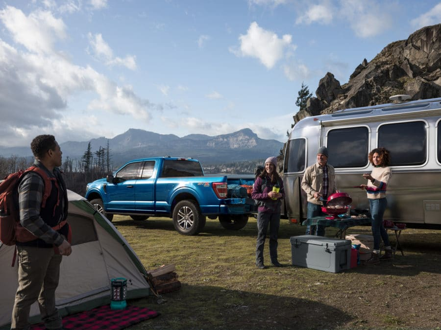 Family and friends camping, with a F-150 and airstream trailer. - Built Ford Tough