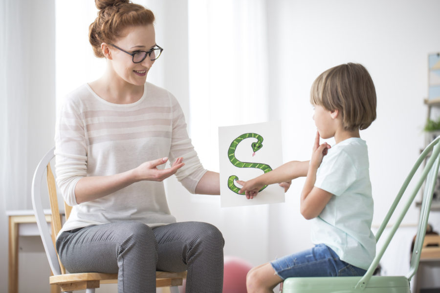 Woman pathologists teaching young boy the letter S