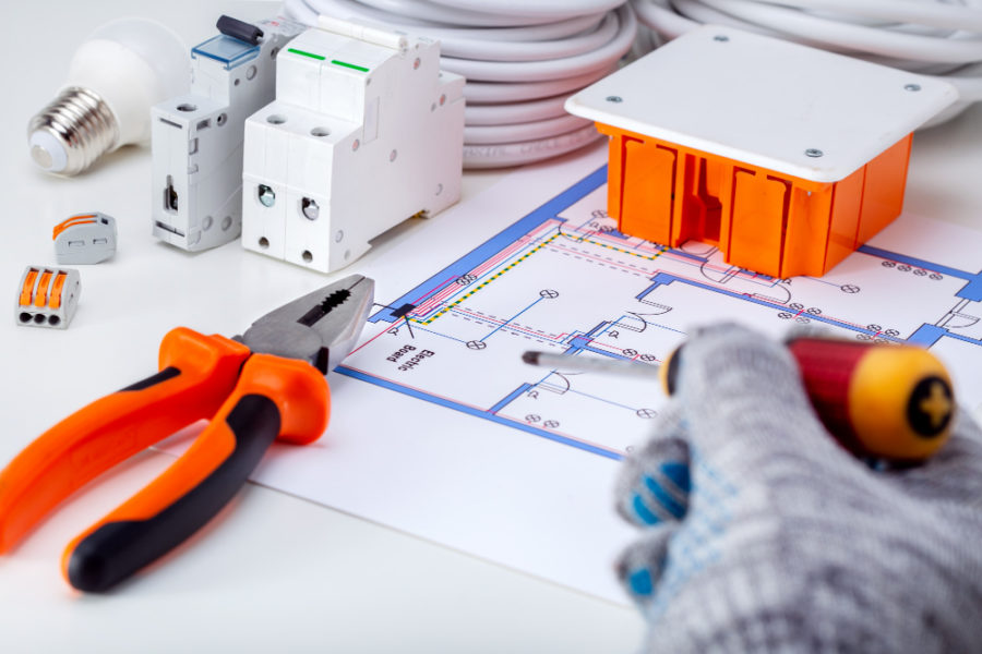 Electrician working with electrical scheme