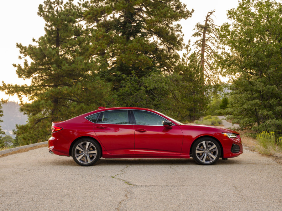 Red 2021 TLX parked in the middle of the road, with trees in the background