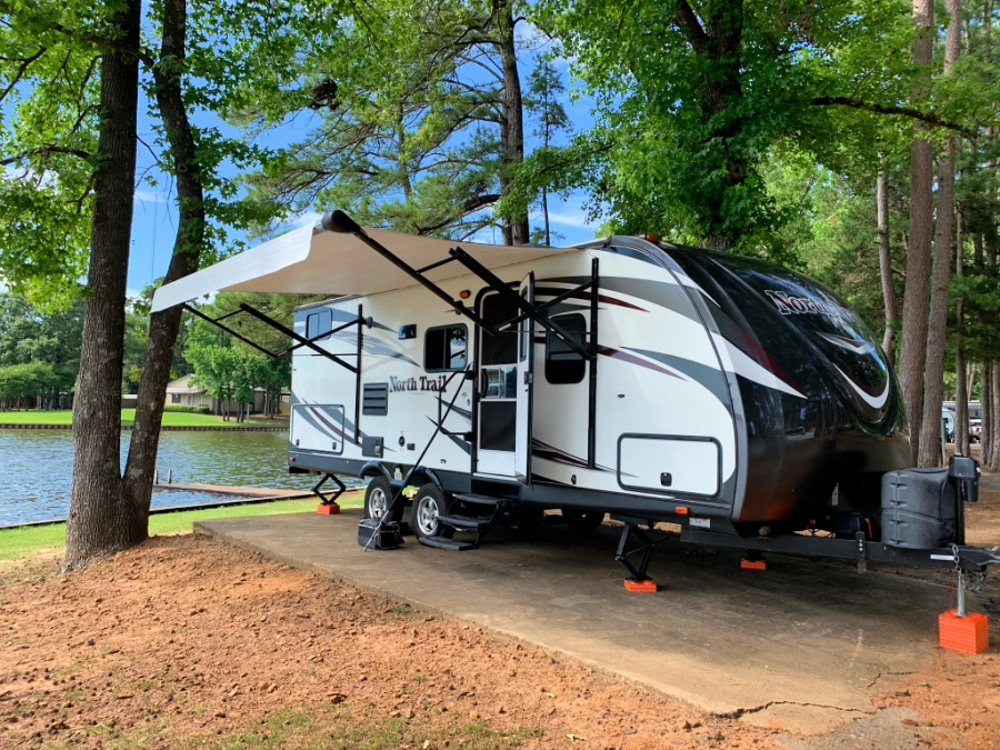 Travel Trailer parked near a lake in a campground