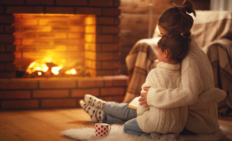 Mother and Daughter sit near fireplace