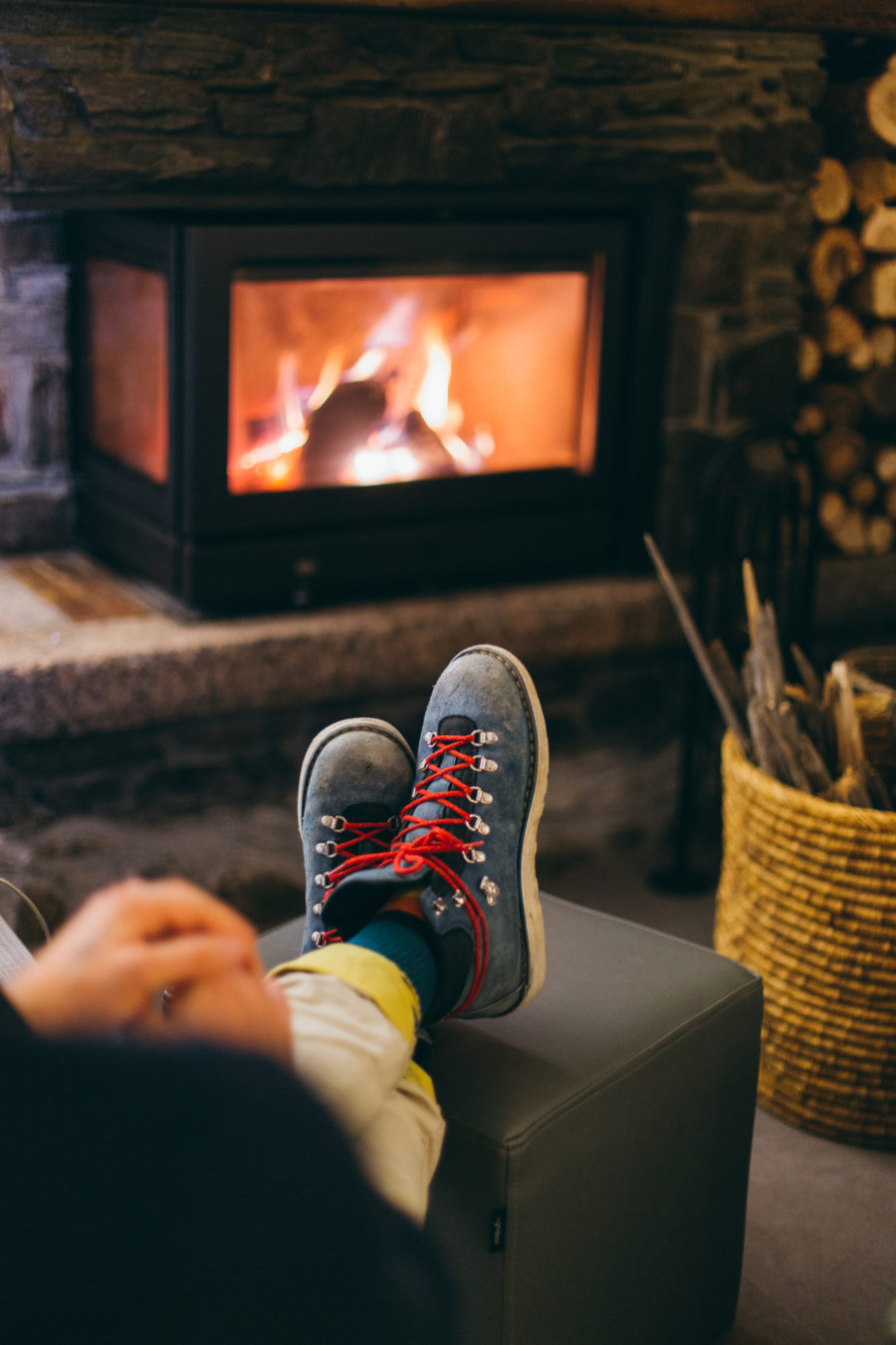 Traveller or tourist rests near the fireplace with their feet up
