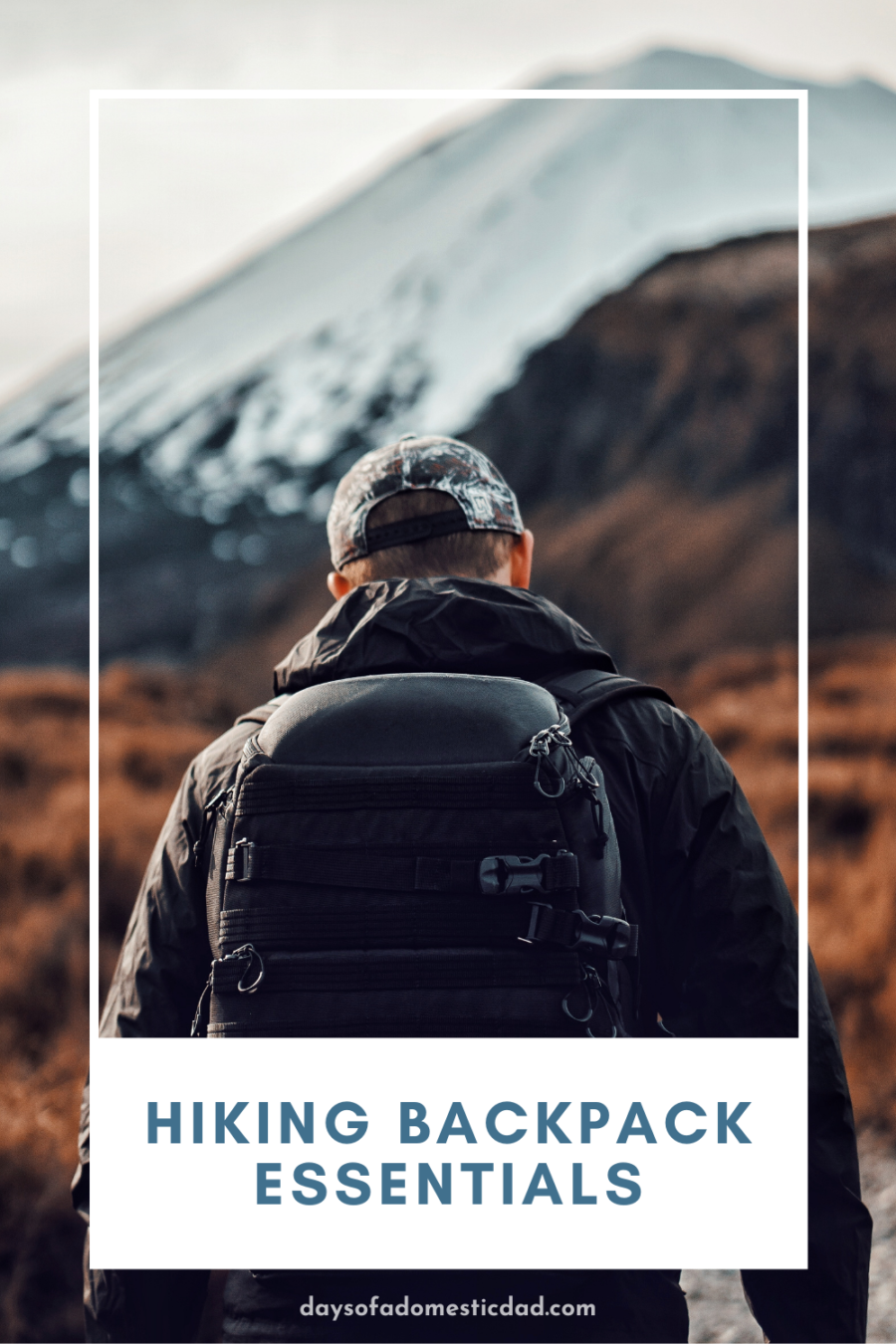 male hiking towards mountain with a backpack