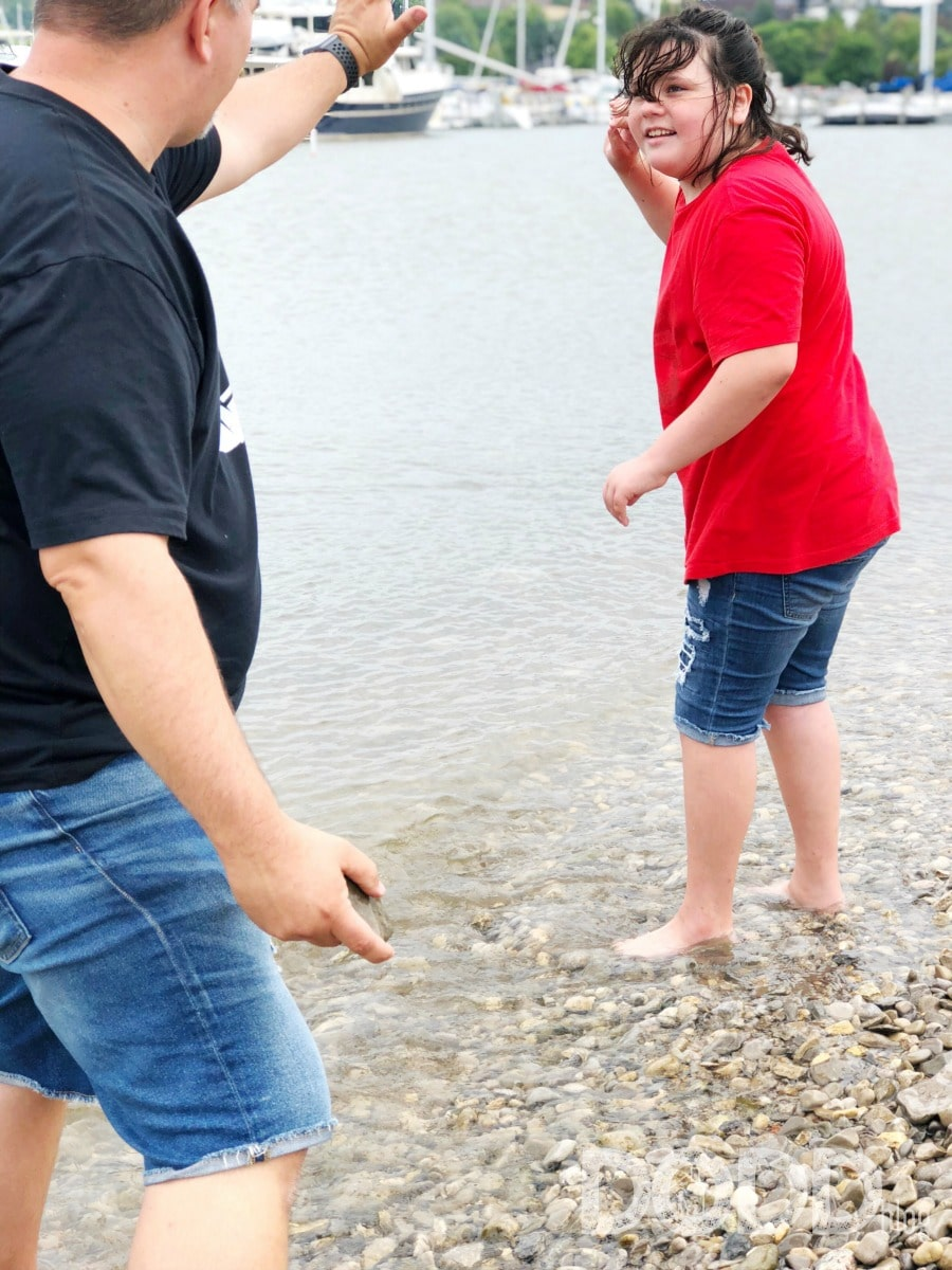 dad and daughter skipping rocks in Lake Michigan