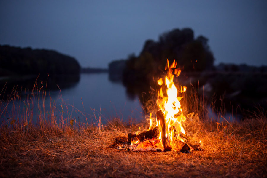 Perfect Family Campground! Bonfire on the bank of the river in the evening. atmospheric photo of a campfire near the river