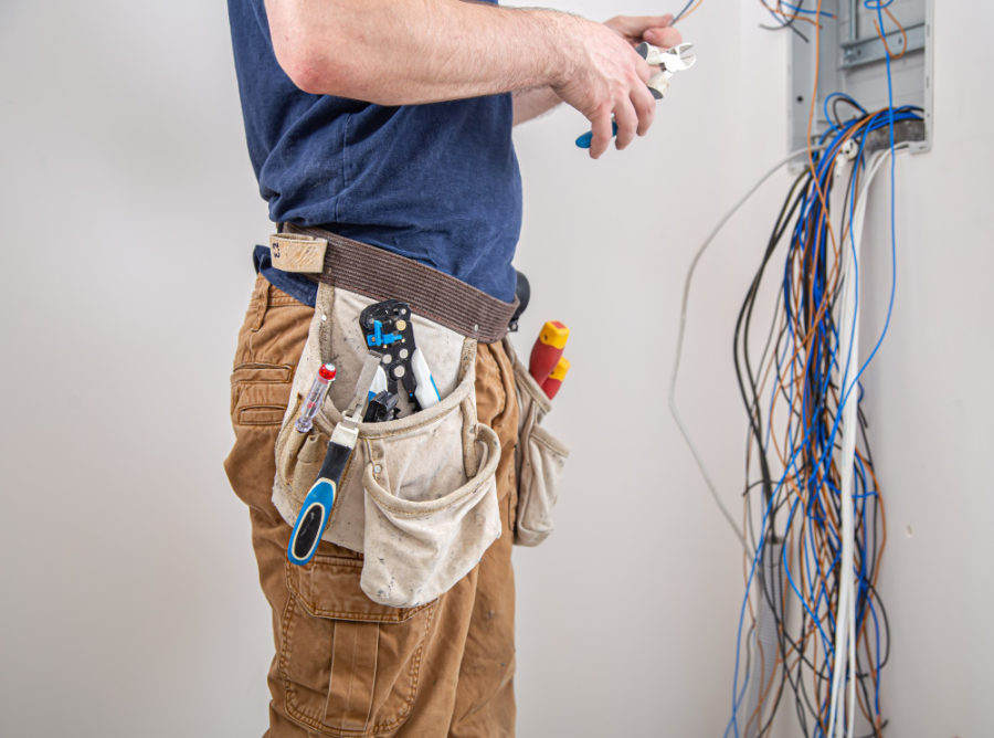 Electrician builder at work, examines the cable connection in the electrical line in the fuselage of an industrial switchboard. professional in overalls with an electrician's tool.