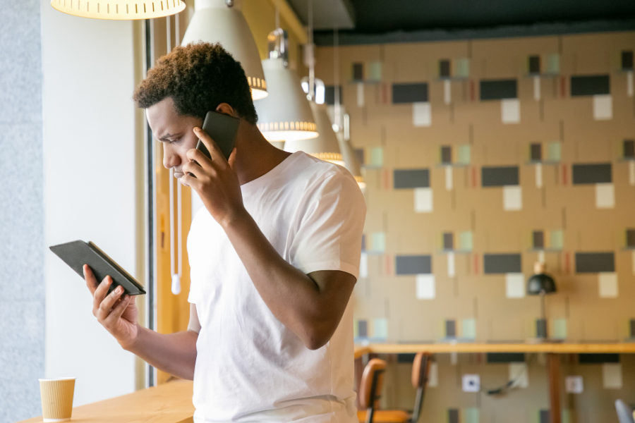 Focused african american guy talking on cell and looking at tablet screen