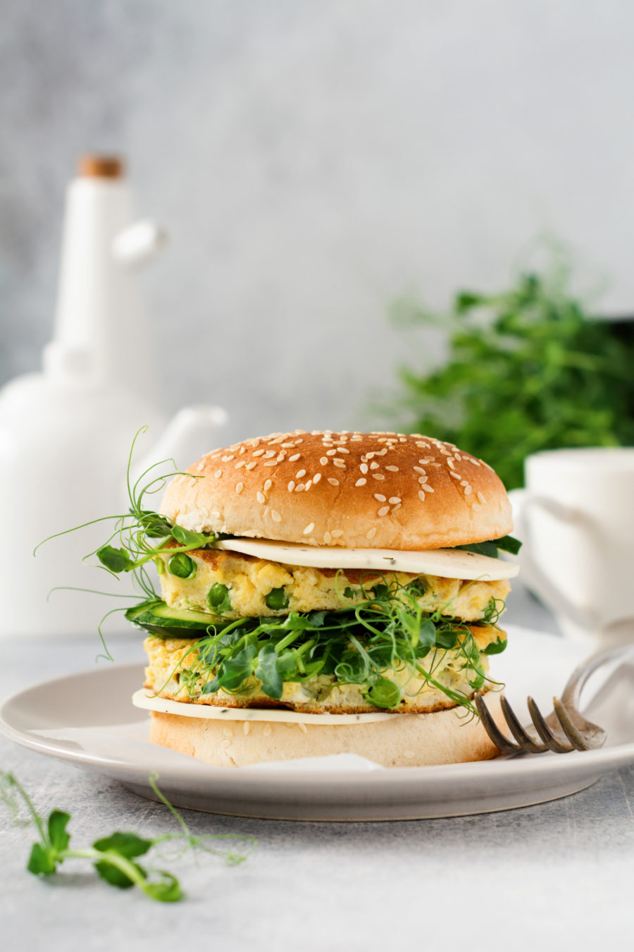 Healthy vegetarian burger with egg and pea shoots and seeds microgreen, fresh salad, cucumber slice on a cutting wooden board on light background. Meatless Monday Recipes