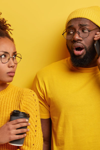 Upset jealous afro wife looks at husband who talks on mobile phone