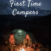 Two young adults camping in the dark, camp fire