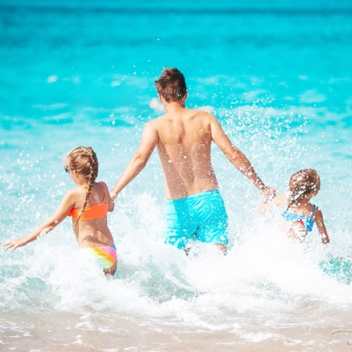 Happy father and little daughters on beach vacation play in shallow water